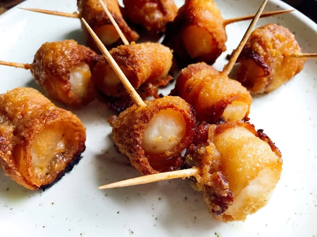 Perfect for holiday entertaining and game day!  These sweet yet spicy snacks are a great appetizer.  Use pork or turkey bacon.  The glaze of brown sugar and mustard caramelizes for a delicious app!  Three Olives Branch | Bacon Wrapped Waterchestnuts | www.threeolivesbranch.com