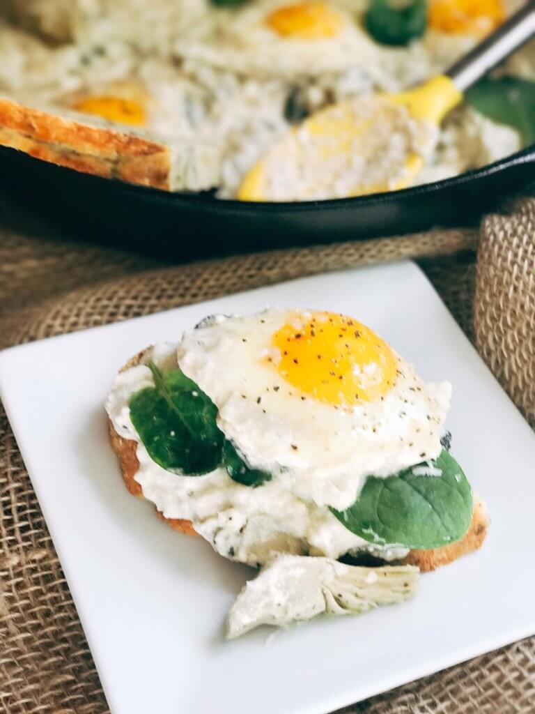 Less than 30 minutes for a simple, filling vegetarian dish that is perfect for breakfast, brunch, lunch or dinner. Also called Eggs in Purgatory, this twist on a classic dish is fast and easy and based on spinach artichoke dip. A creamy Parmesan cheese sauce is the base for the eggs, spinach, artichoke, and cheeses. Serve on top of bread for a filling meal! Spinach Artichoke Shakshuka | Three Olives Branch | www.threeolivesbranch.com