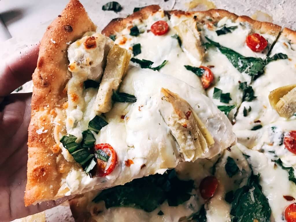 Perfect for dinner parties and fun meals, this pizza is based on the classic spinach artichoke dip! Spinach, artichoke hearts, Parmesan, cream cheese, garlic, and more form a dip as the sauce of this pizza with additional veggies like tomatoes or your favorite meats as the toppings. Try it out with our Parmesan Black Pepper or Rosemary Garlic Pizza Doughs. Make the dough in advance for a faster meal! Freezes well, kid friendly, vegetarian, and delicious! Spinach Artichoke Dip Pizza   Three Olives Branch   www.threeolivesbranch.com