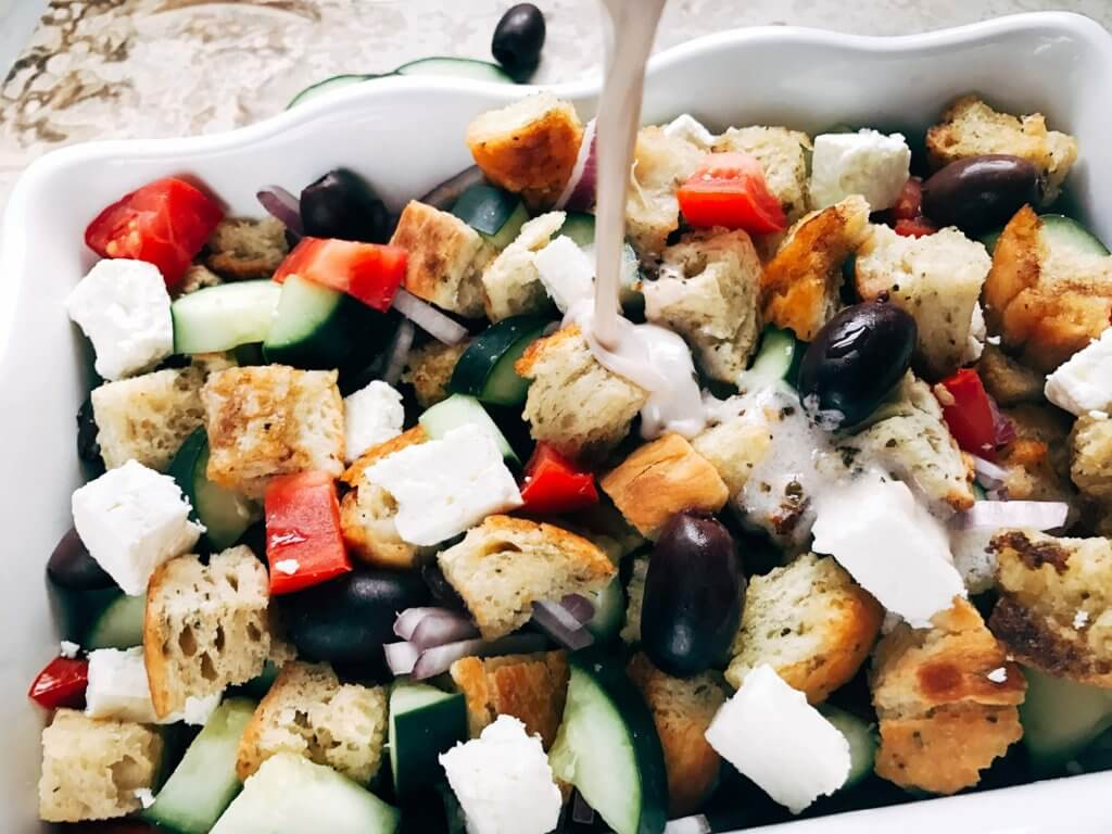 Traditional Italian salad combined with a Greek salad. Simple to make and a perfect side dish for your summer grilling party or BBQ gathering, Father's Day, 4th of July, and more. Bread chunks are tossed with Greek salad ingredients of feta cheese, kalamata olives, red onion, cucumber, and tomatoes with a creamy vinaigrette made from Greek yogurt, oregano, oil, and red wine vinegar. Simple to make and a unique side dish to show off! Creamy Greek Panzanella Salad   Three Olives Branch   www.threeolivesbranch.com