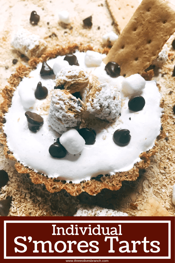 A fun dessert perfect for summer activities like 4th of July and camping. A graham cracker crust is made out of ground Post Shredded Wheat Frosted S'mores Bites Cereal, then filled with melted chocolate, marshmallow fluff, and topped off with some decorations. A fun sweet treat in an individual tart. Individual S'mores Tarts #smores #summerrecipes #campingrecipes