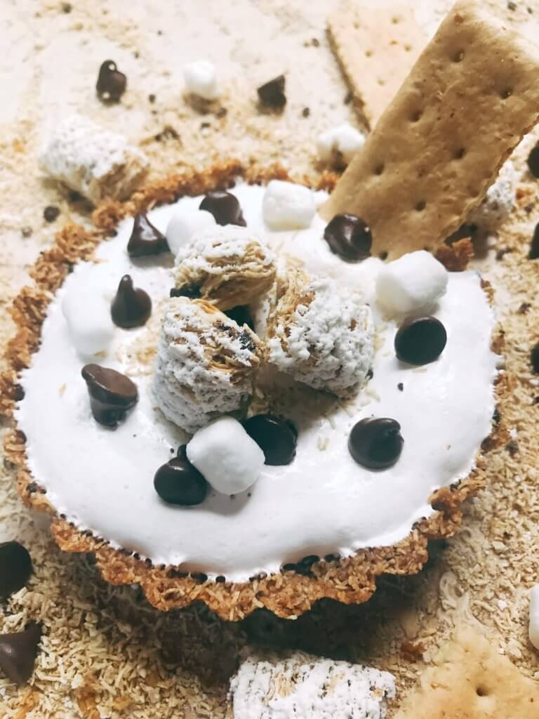 A fun dessert perfect for summer activities like 4th of July and camping. A graham cracker crust is made out of ground Post Shredded Wheat Frosted S'mores Bites Cereal, then filled with melted chocolate, marshmallow fluff, and topped off with some decorations. A fun sweet treat in an individual tart. Individual S'mores Tarts | Three Olives Branch | www.threeolivesbranch.com