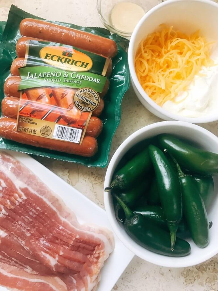 Grill up some of these smoky, cheesy treats for your next summer party. Eckrich Cheddar and Jalapeno Smoked Sausage is stuffed with a jalapeno pepper (which has been filled with cheddar and cream cheese), then rolled in bacon and grilled until crispy. They make such a fun appetizer or dinner for the pork lovers. A fun twist on a jalapeno popper and full of flavor. A great way to kick of football Sunday or game day. Cheddar Jalapeno Smoked Sausage Bacon Bombs   Three Olives Branch   www.threeolivesbranch.com