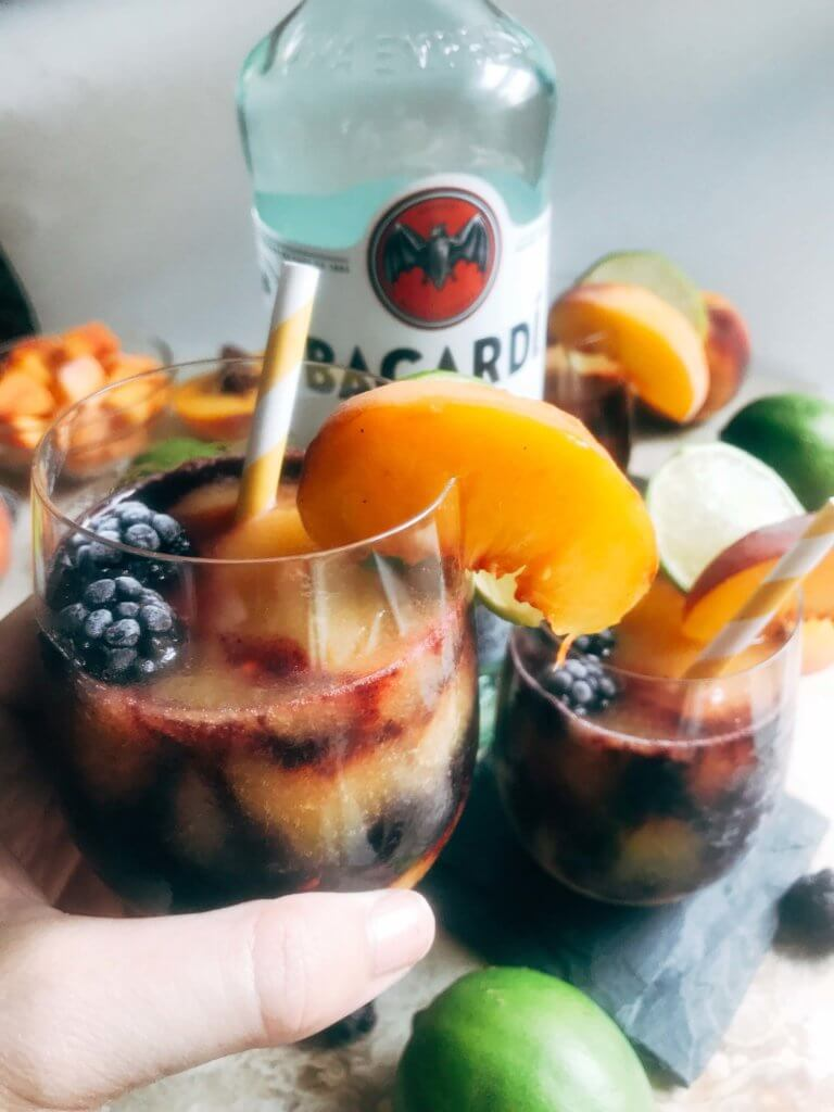 A quick and simple blended alcoholic beverage perfect for warm summer weather. Peaches and blackberries are blended with Bacardi Superior Rum, simple syrup, and lime to make this frozen layered drink. Just 10 minutes for this easy cocktail. Vegan, vegetarian. Blackberry Peach Frozen Daiquiri   Three Olives Branch   www.threeolivesbranch.com