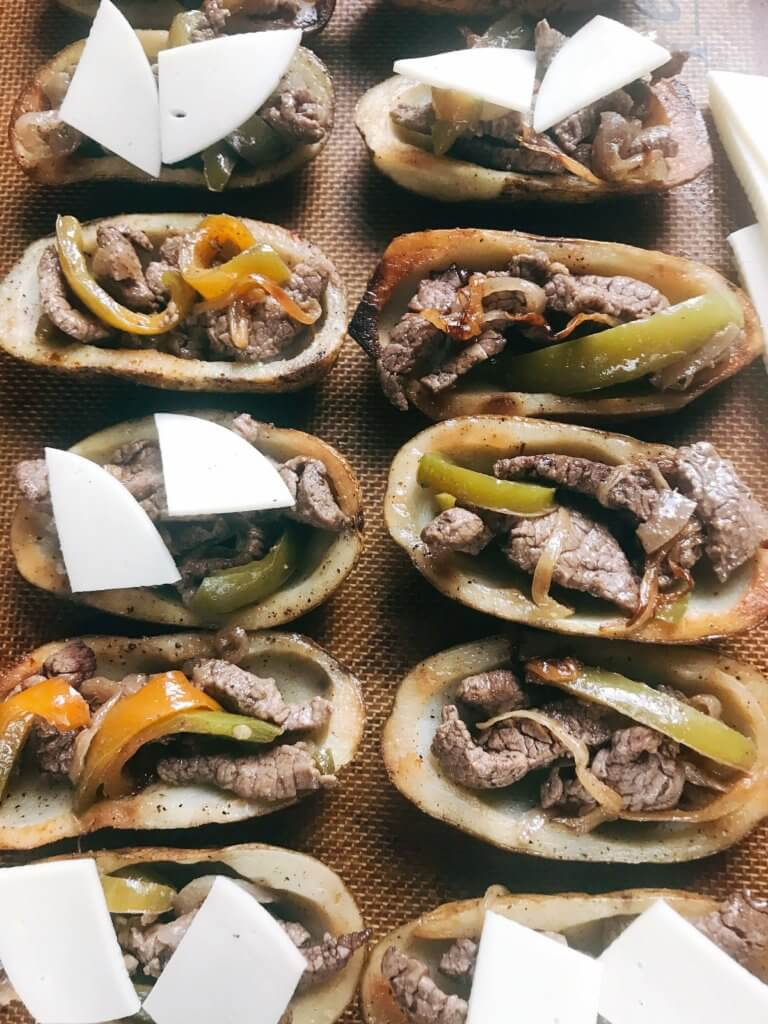 Game day appetizer full of classic Philly Cheese Steak flavors. Beef steak, bell peppers, onion, and provolone cheese in a potato skin shell. Great football food for NFL Sunday as a party snack. Gluten free. Philly Cheesesteak Potato Skins | Three Olives Branch | www.threeolivesbranch.com