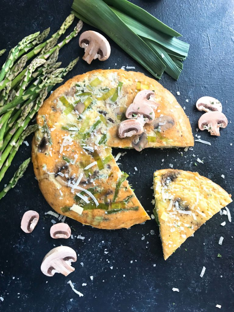 A quick and simple breakfast or brunch recipe ready in 20 minutes. Vegetarian and gluten free, this frittata is similar to an omelette and perfect for holidays like Easter and feeding a crowd. Asparagus, Leek, and Mushroom Parmesan Frittata | Three Olives Branch | www.threeolivesbranch.com #breakfastrecipe #vegetarianbreakfast #easterbrunch #springbreakfast