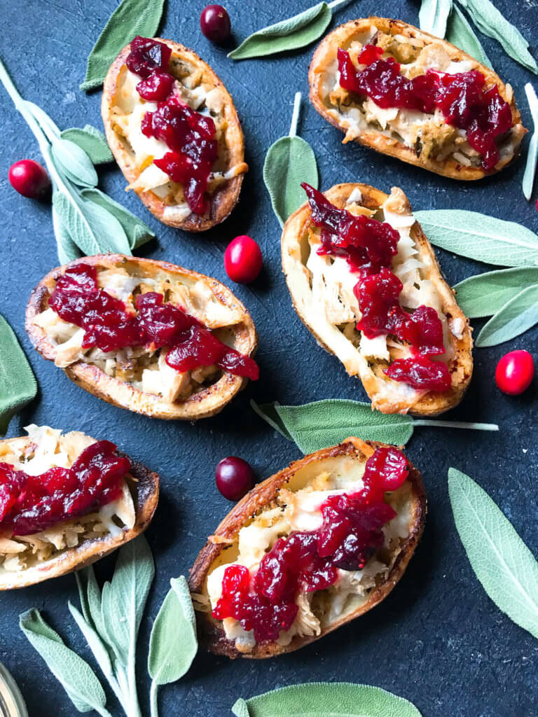 A fun recipe to use leftover Thanksgiving food! Stuffing, turkey, and cheese are layered in a potato skin shell and topped with cranberry sauce and gravy. Use any leftover like green bean casserole! Thanksgiving Leftovers Potato Skins | Three Olives Branch | www.threeolivesbranch.com #thanksgivingrecipes #thanksgivingleftovers