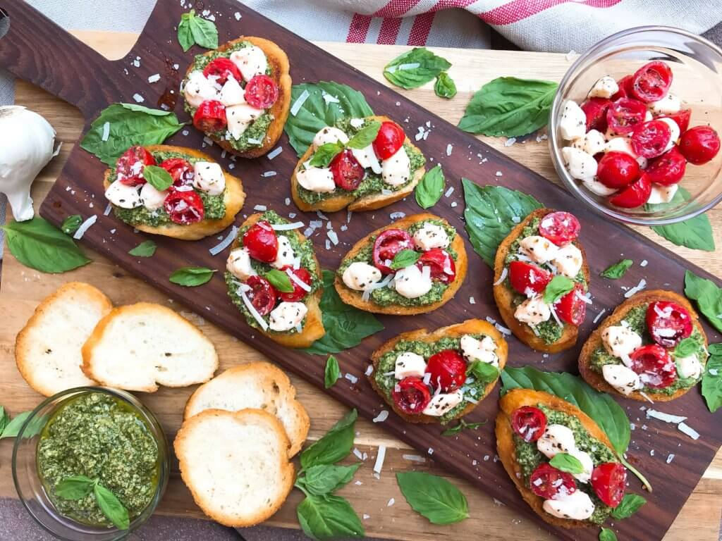Ready in less than 30 minutes, this party finger food appetizer is full of bright and fresh flavors. Crostini bread is topped with basil pesto, cherry tomatoes, and fresh mozzarella. Vegetarian. Caprese Pesto Crostini #appetizers #caprese #pesto #italianrecipe
