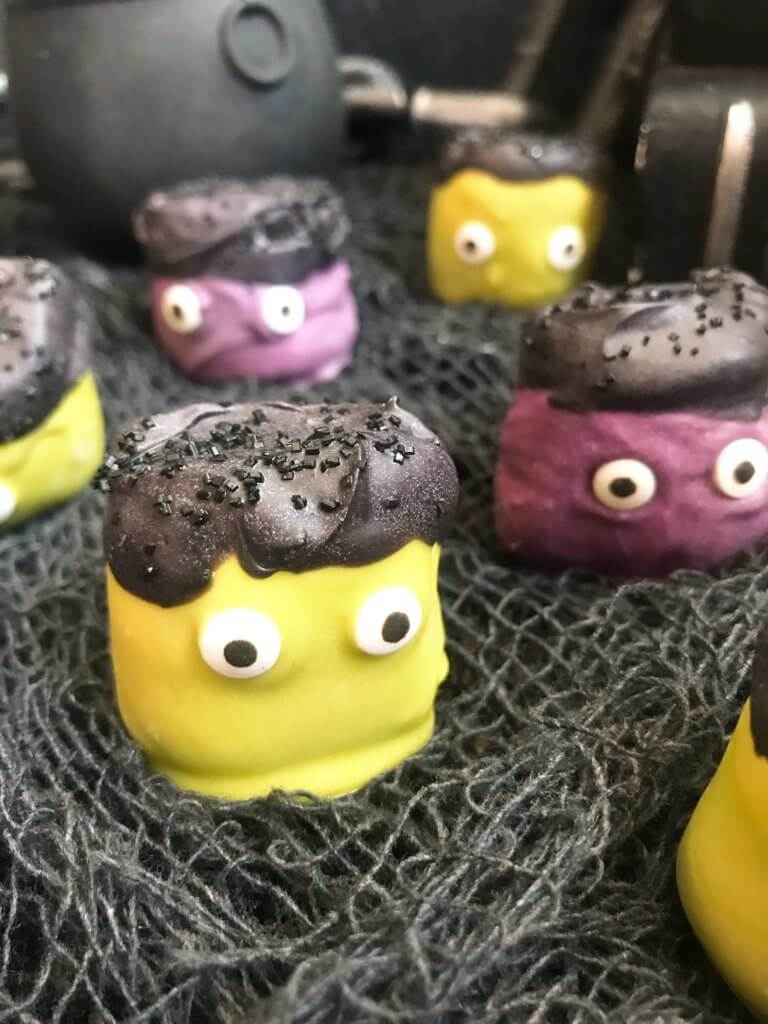 Simple and easy Halloween treat dessert recipe. Halloween Candy Dipped Monster Marshmallows are large marshmallows dunked in colored candy melts with sprinkles and candy eyes for your Halloween party. #halloweenfood #halloweenrecipes #halloweenparty #monsterparty