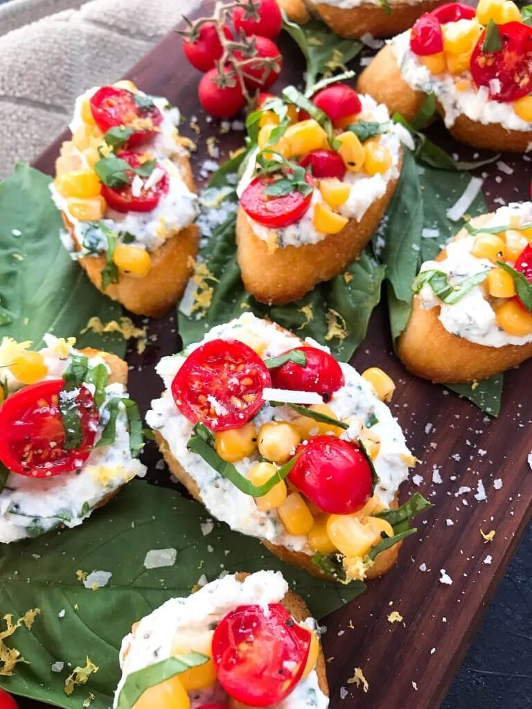 Fresh cherry tomatoes, basil, and corn are mixed with lemon. Ricotta and Parmesan cheese are mixed with lemon and herbs then layered on toasted bread slices. Tomato Corn Basil Crostini with Herbed Ricotta Cheese are vegetarian and perfect party and summer entertaining food. #fingerfood #summerappetizer #crostini