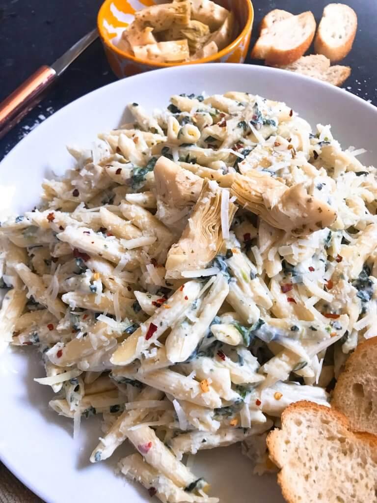 Spinach Artichoke Dip Pasta ready in less than 30 minutes. A cheesy Italian pasta recipe made with three cheeses: Parmesan, cream cheese, and Monterey Jack. Vegetarian. #spinachartichokedip #pastarecipe #italianrecipe