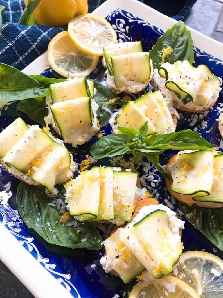 Ready in 30 minutes, Zucchini Lemon Ricotta Crostini are a perfect Italian appetizer recipe. Fresh lemon herb ricotta is layered with zucchini ribbon slices on baguette bread slices. Great for summer party and entertaining food. Vegetarian. #crostini #zucchinilemon #summerappetizer