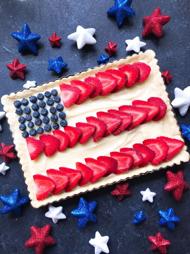 A quick and simple red, white, and blue dessert ready in 30 minutes. Patriotic American Flag Fruit Tart is a lemon cream cheese tart with fresh strawberries and blueberries. Great recipe for Labor Day, Memorial Day, and 4th of July BBQ or cookout. #americanrecipes #redwhitebluerecipes #redwhitebluedessert #fruittart