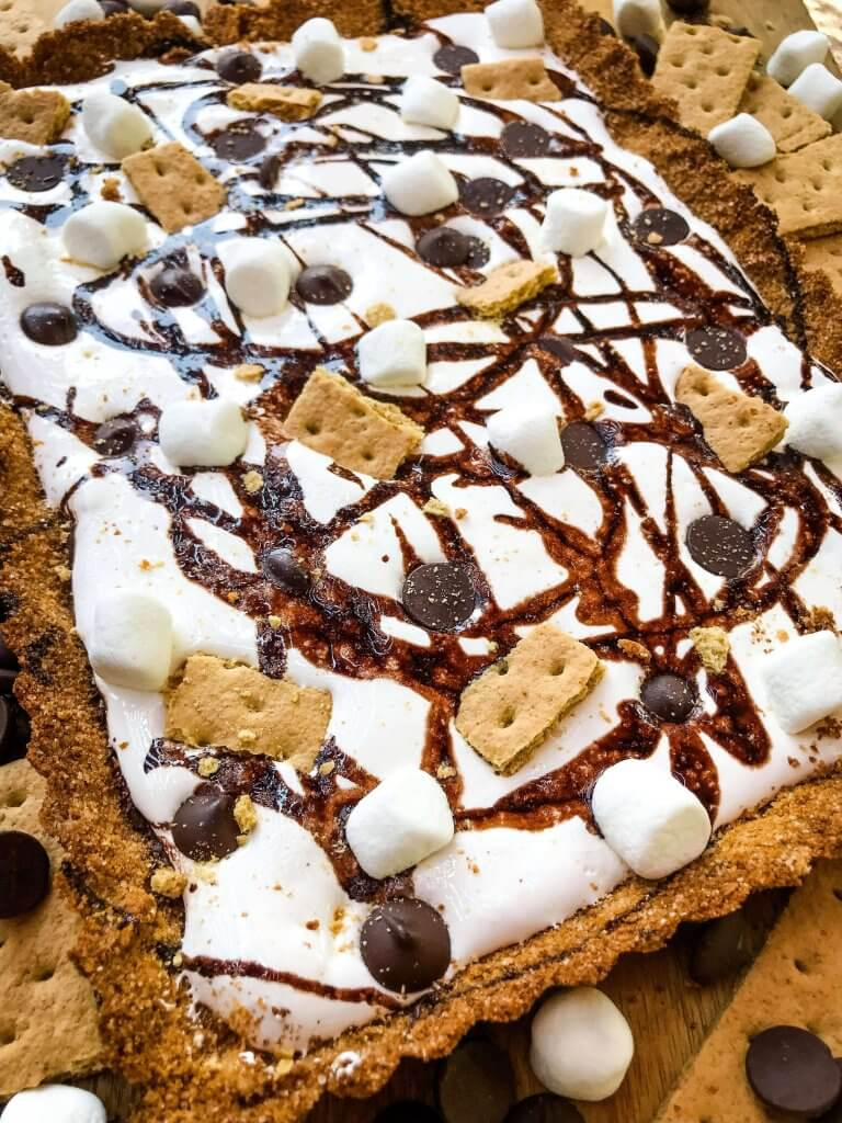 A S'mores Tart for summer dessert recipes. A graham cracker crust is filled with melted chocolate, marshmallow fluff, and s'mores ingredients. Simple and easy. #smores #tartrecipe