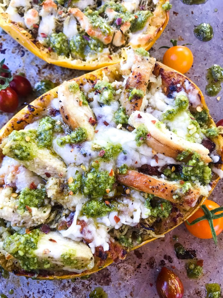 Keto Low Carb Cheesy Chicken Pesto Spaghetti Squash is a gluten free dinner recipe. Sliced chicken is mixed with basil pesto and cheese in a squash shell for a healthy meal and twist on pesto pasta. #spaghettisquashrecipes #stuffedspaghettisquash #pesto