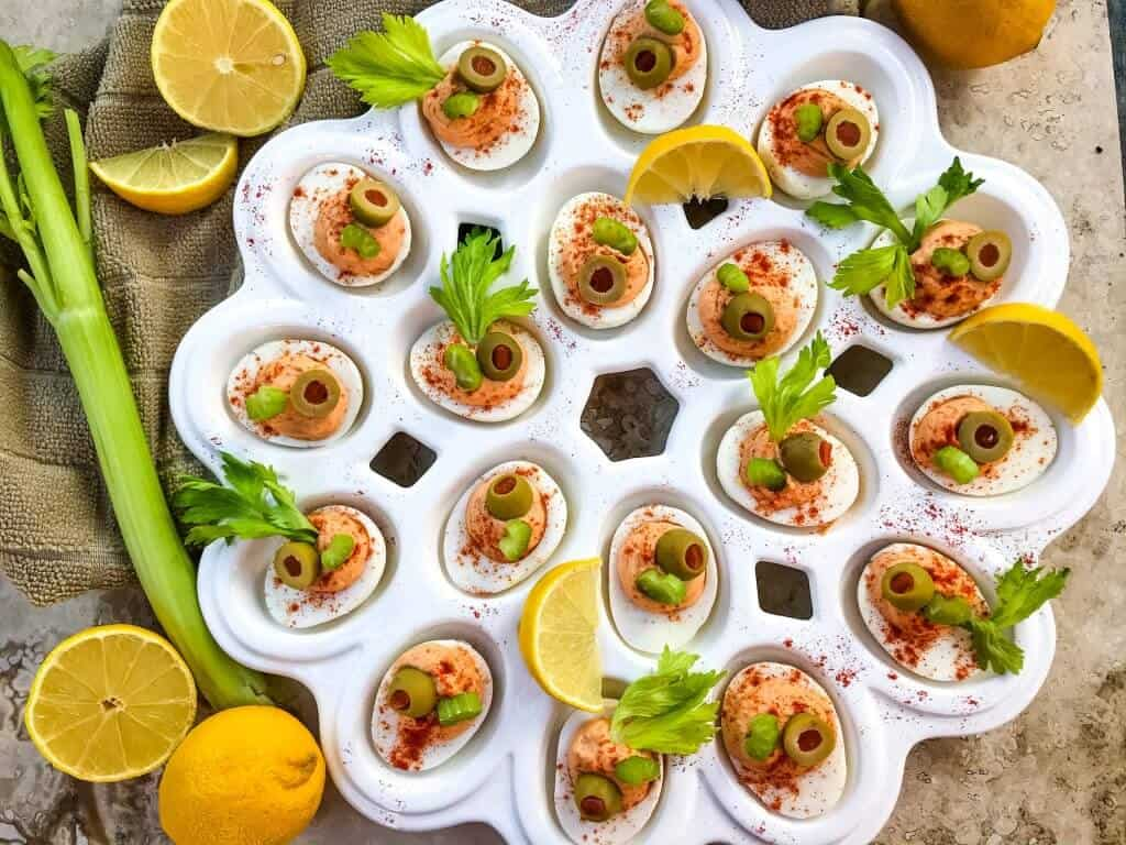 Bloody Mary Deviled Eggs recipe using the same cocktail ingredients. Tomato, celery salt, garlic, Worcestershire, and lemon in a fun game day and party appetizer finger food. #deviledeggs #bloodymary #gamedayrecipes