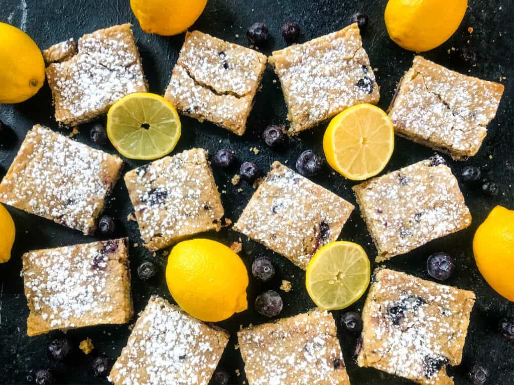 Lemon Blueberry Blondie Recipe is a cross between soft cookie bar and brownie filled with fresh blueberries and lemon. A great spring dessert. #blondies #blueberrylemon