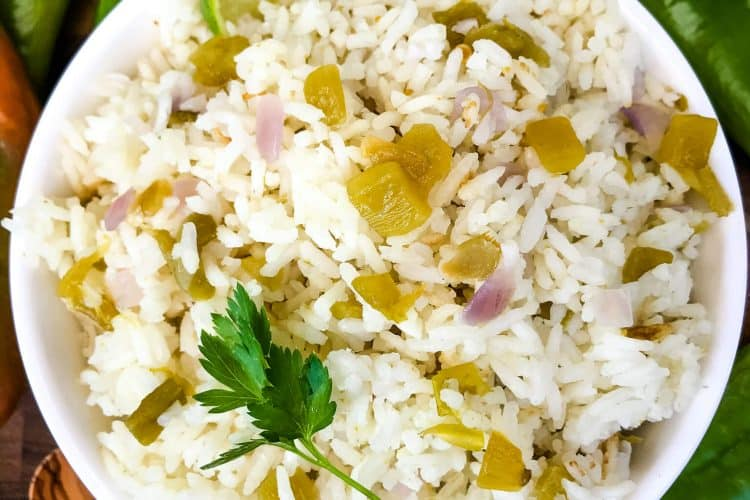 Bowl filled with Hatch Green Chile Rice surrounded by peppers