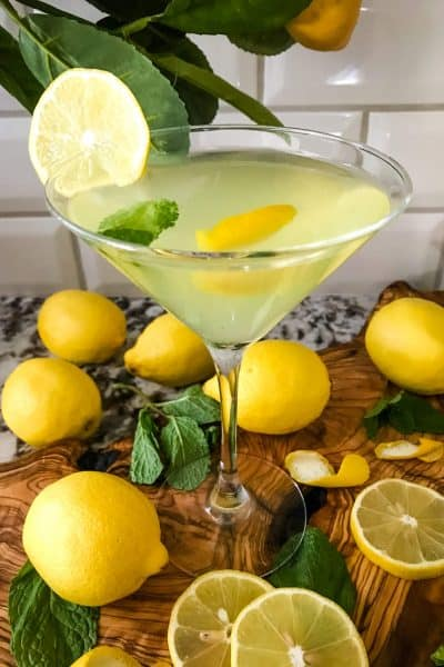 A martini glass full of Amalfi Martini Limoncello surrounded by lemons and mint