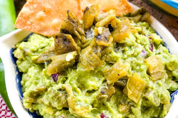 A bowl of Hatch Green Chile Guacamole with some chips sticking out of it