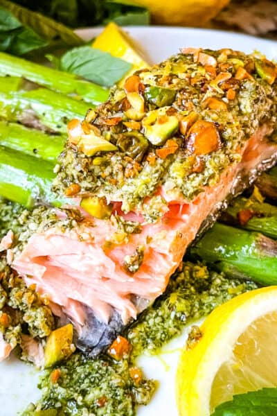 Pesto Crusted Salmon partially eaten on top of asparagus