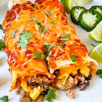 Two Southwest Ground Turkey Enchiladas on a plate with cilantro and limes