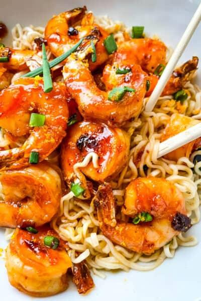 Chipotle Orange Glazed Shrimp in a bowl on top of ramen noodles with chopsticks