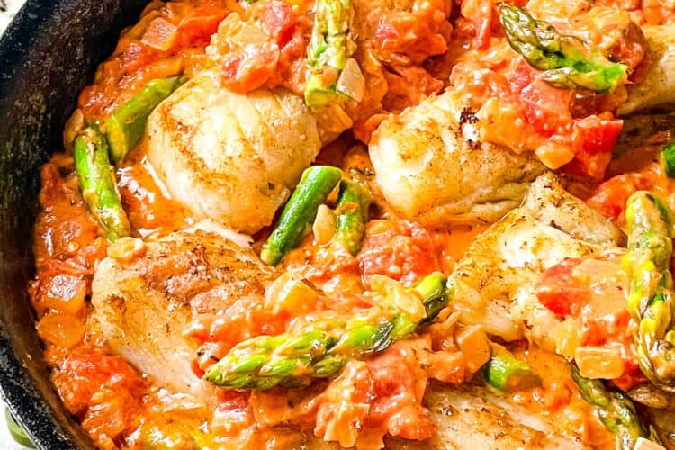 Cod Pomodoro with Asparagus in a black skillet
