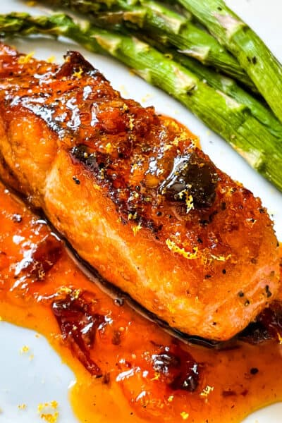 A cooked Chipotle Orange Glazed Salmon steak with sauce under it on a plate
