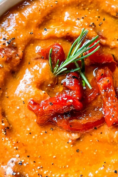 Close up of the dip with peppers and rosemary on top