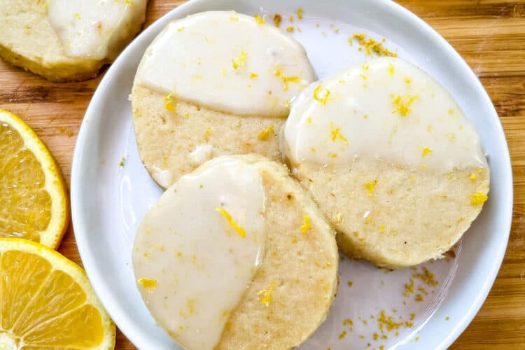A white round plate with three Lemon Shortbread dipped in glaze surrounded by lemon slices and more cookies