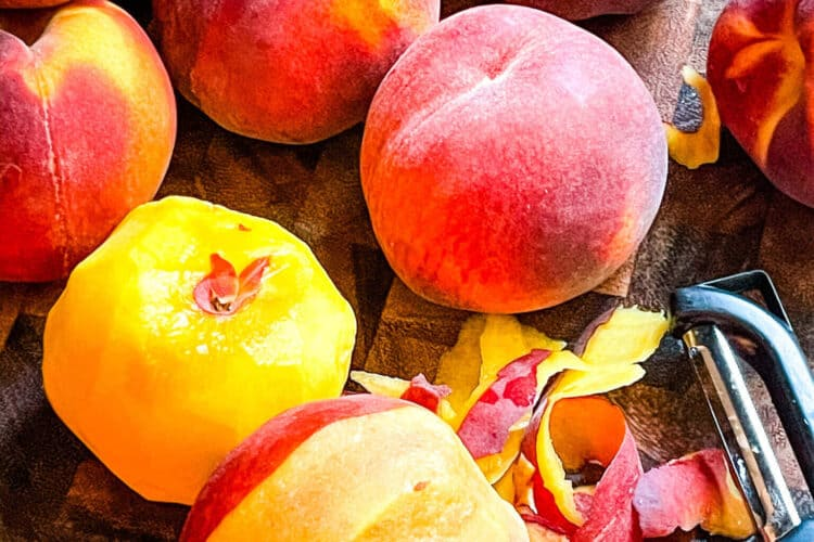 A pile of peaches with one partially peeled