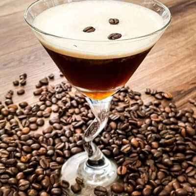 A glass full of the coffee cocktail with beans all around it