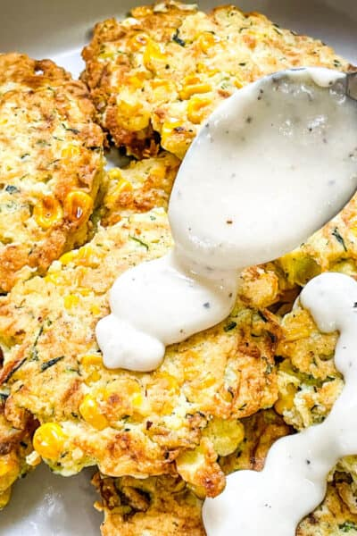 A spoon pouring white gravy over Corn and Zucchini Fritters